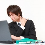 パソコンにより肩こり・目の疲れに悩む男性
